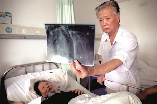 图为:周爹爹出示老伴受伤部位的X光片 见习记者姚品 实习生段文俊摄