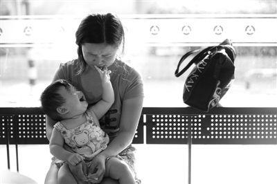 昨日,肯德基京广中心店门口,姜女士提起跟养父母的关系时落泪,怀中9个月的女儿笑着跟她玩。新京报记者 薛珺 摄