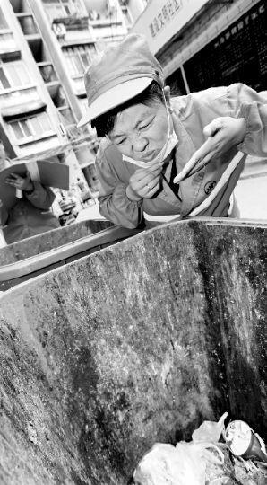 """""""闻臭师""""正在辨别社区垃圾桶里的臭味级别。本报记者 傅坚 摄"""