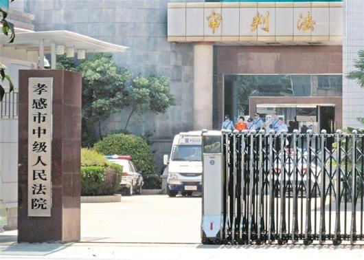 图为:庭审结束后吴某被押上警车