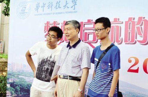 昨日,15岁的张赛瑞(最右)和华科校长李培根(中间)合影。华中科技大学供图