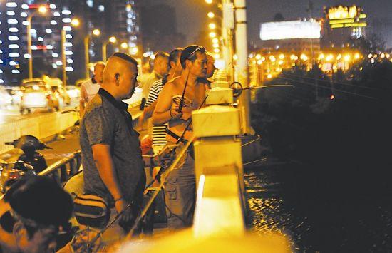 图为:夜色中的知音桥上,聚集着众多垂钓者