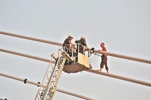 图为:救援人员乘坐云梯劝说陈某
