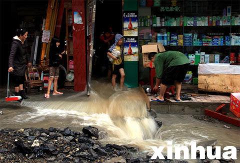9月10日,积水从湖北省宣恩县长潭河乡集镇的一家店铺涌向街道。