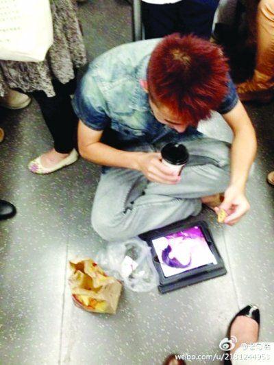 早高峰男子席地坐在地铁车厢内进食。 岳先生提供