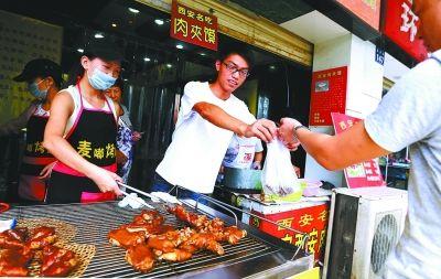 图为:周志杰(中)和女友一起卖烤猪蹄,生意挺不错的。 记者何晓刚 摄
