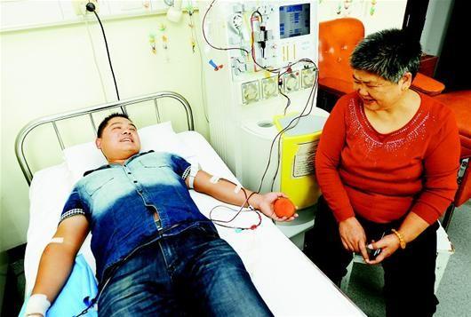 图为:粱啸的母亲陪在病床边。(记者 张朋 摄)