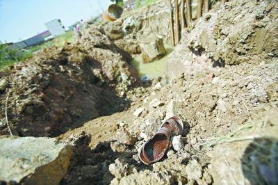 急于救人遇难的周姓工人的鞋还遗留在坑边 记者陈卓 摄(实习生 郑永贞)