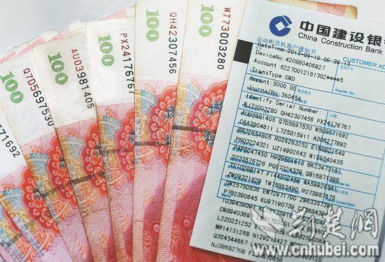 图为:记者的取款凭单上记录着钞票的冠字号 记者朱熙勇摄