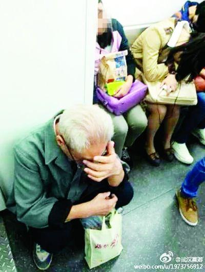 ▲在地铁里一位白发老爷爷没有座位,只能掩面蹲下。(网友夏先生 摄)