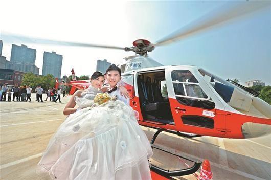 图为:新郎抱着新娘走下直升飞机