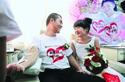 新郎仝赛赛以献血的方式来见证他们的爱情,新娘则坐在一旁守护 见习记者胡琴沁 摄