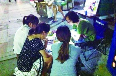 刘蕾正在给顾客贴手机膜。记者陈浩然 摄