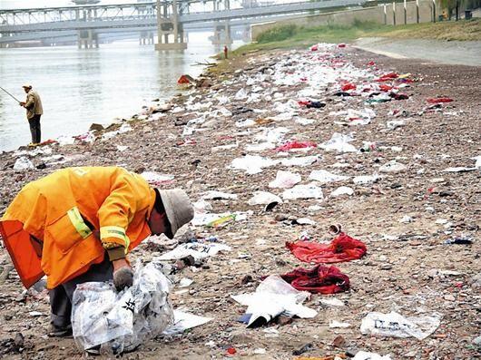 楚天都市报讯 图为:昨日清晨,环卫工人清理汉口江滩临水带垃圾