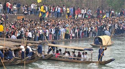 昨日,大量游客在沱江边排队等候上船游览,长假第4天,凤凰古城迎来旅游高峰,古城内大街小巷的数万游客摩肩接踵。新华社记者 龙弘涛 摄