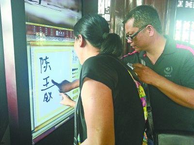 """图为一对游客夫妻在""""涂鸦""""。记者谢东波 摄"""