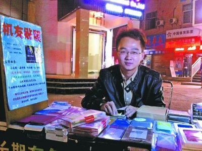 傅磊在他经营的夜市手机贴膜小摊上。