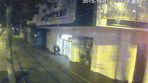 图为:1日凌晨3时许周某行劫时与储户扭打 视频截图
