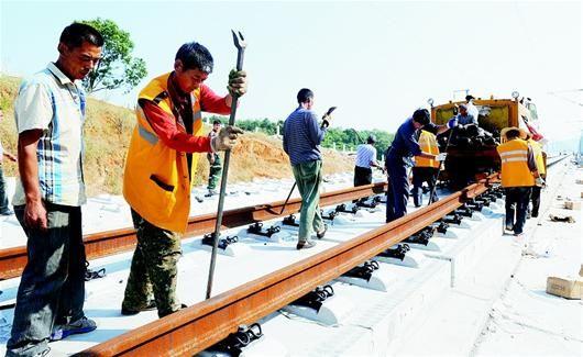 桥面钢轨已从武汉站铺过鄂州花湖,即将到达黄石,工人们正在调整钢轨