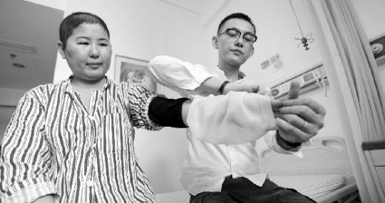 昨日,协和医院肿瘤中心,叶诗琪(右)正在演示如何使用硅胶护具。本报记者 傅坚 摄