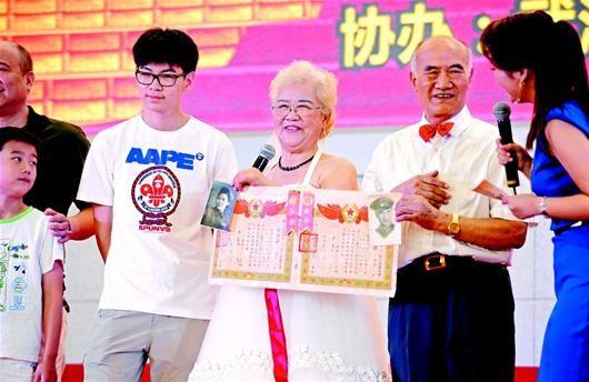 图为:陈素芳(左)和刘金龙上台展示当年的结婚证。 (记者 李溪 摄)