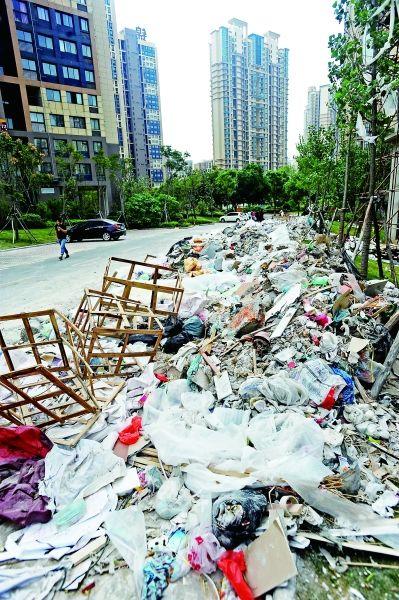 昨日,锦绣龙城小区里,成堆暴露的建筑垃圾绵延上百米。记者苗剑 摄