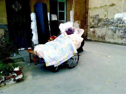 图为:老人守着棺材露宿街头。