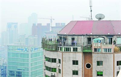 昨日城管执法人员拆除三阳广场33楼的屋顶违建房记者刘斌 摄 (信息来源:顾丹 实习生李若蓝)