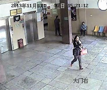 图为:女子抱着婴儿走出住院部大厅