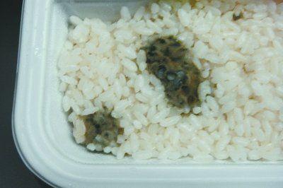 图为盒饭里发霉的大米。 记者明眺生 摄