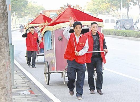 志愿者协助马成银(挥手者)拉着感恩板车
