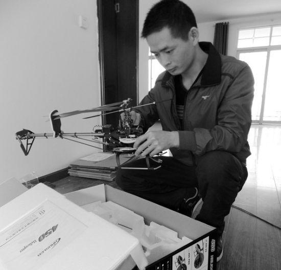 图为:陈克朋展示直升机模型