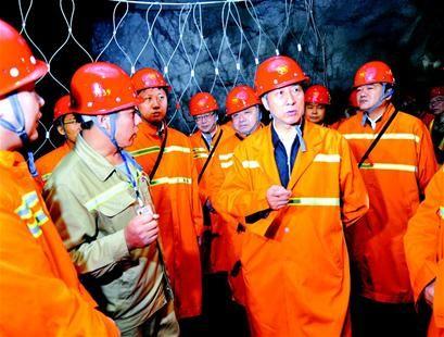 图为:王勇(右前)在井下与工人交流。