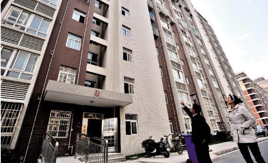 图为:站在新建的居民楼下,被骗的程军夫妇望房兴叹