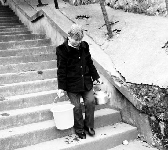 图为:当地一位婆婆在提水 (记者朱娟娟摄)