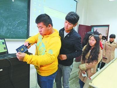图为学生们正在扫描学生证。