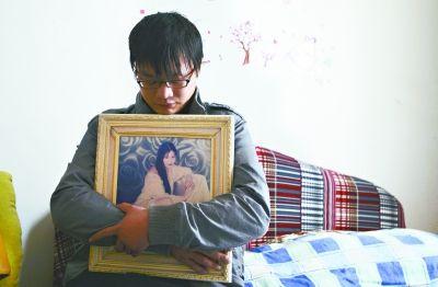 儿子詹蕾悲伤地抱着妈妈年轻时的艺术照 见习记者胡琴沁 摄