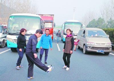 不少武汉大妈为了打发堵车时间,召集周围司机下车踢毽子