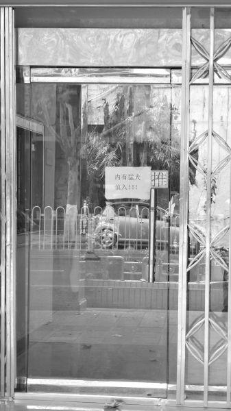 """图为市城市排水监测站汉口分站大门的玻璃门上贴着""""内有猛犬,慎入""""字样"""