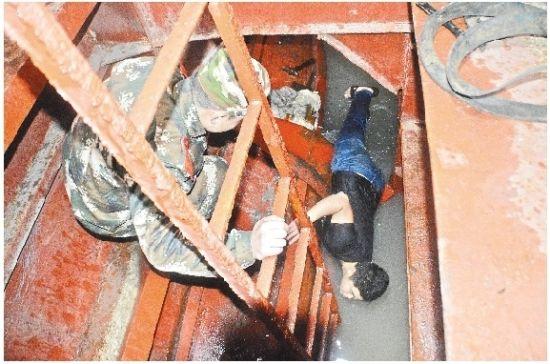 图为:武警船艇大队官兵帮助船员堵漏、排水