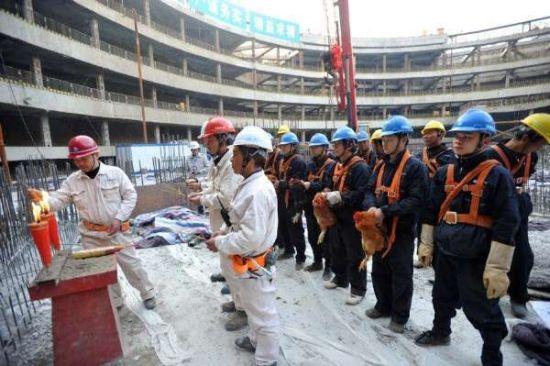 """2013年1月4日下午,华中在建第一高楼""""武汉绿地中心""""举行首根钢巨柱吊装仪式。图为仪式现场设祭坛,绑活鸡祭祀。"""