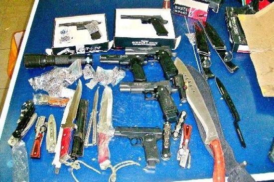 图为:武汉警方收缴黑恶团伙的枪支、弹药、管制刀具等
