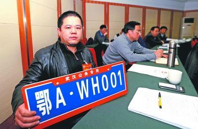 许方辉委员展示公务专用车牌模型。记者何晓刚 摄
