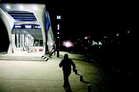 湖北日报讯 图为:5日22时许,一男子快步跑入地铁4号线园林路站,因周边团结大道通车后未亮灯,附近居民只能摸黑乘车,地铁站成了整条马路上唯一亮灯的建筑。(记者 成熔兴 摄)