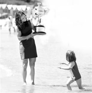 图为:昨日,李娜在墨尔本海滩展示澳网冠军奖杯(新华社发)