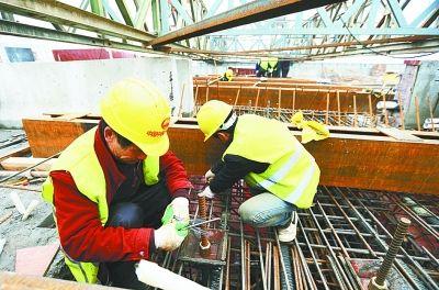 工人师傅正在加紧大桥合龙段的施工。记者何晓刚 摄(图片来自 武汉晚报 )