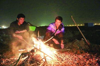 两大学生工地上 点起篝火过除夕