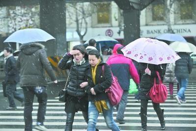 昨日下午,在汉口解放大道航空路附近,行人从纷飞的雪花中走过 记者李永刚 摄