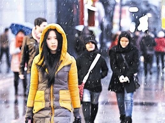 图为:纷纷落雪伴着行人,成为昨日江城的一道风景 (记者宋双庆摄)