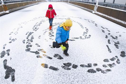 图为:因大雪而封闭的高架桥,成了娃娃们的玩雪场(记者万多摄)